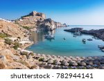 Small photo of St. Paul´s bay with boats, Lindos acropolis in background (Rhodes, Greece)
