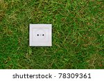 green energy concept: electric outlet on a grass - stock photo