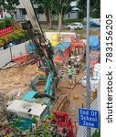 Small photo of Bukit Timah Road, Singapore - December 27, 2017: Underground utility servicing near school zone area. Crawler drilling rig is used. A worker operates an excavator while the other relocates new cables.