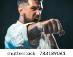 Small photo of Sportsman martial art taekwondo training, in karate position. MMA - Mixed martial art. Selective focus on fist. Portrait of screaming karate master instructor.