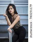 Portrait of a sexy and sensual young Asian woman in trendy clothes leaning on the railing while posing on the stairs outdoors. Fashion summer photo