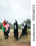 """Small photo of Three female Muslim wearing black abaya and keffiyeh to cover their faces and mafla with Arabic words mean """"We are the frontliners"""" and """"Brigade AlQassam"""", military wing of the Palestinian Hamas"""
