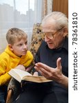 Small photo of grandfather reading book aloud to his grandson, who is listening to him with attention