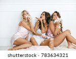 Stock photo beautiful girls at home party having fun happy female friends in stylish lingerie pajamas playing 783634321