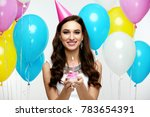 Small photo of Happy Birthday. Girl With Balloons And Cake At Party. Portrait Of Beautiful Smiling Woman In Festive Dress And Birthday Hat Holding Cupcake With Candle In Hands, Celebrating Holiday. High Resolution.