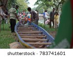 Small photo of SIEM REAP, CAMBODIA - NOVEMBER 2016: Eye level perspective view of boat team members inspecting their long boat before a trial run in Cambodia, Southeast Asia.