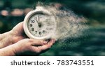 Small photo of Retro alarm clock or vintage alarm clock in old hand. Time is running out concept shows clock that is dissolving away into little particles