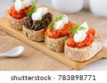 Small photo of Appetizer bruschetta with mozzarella cheese, pepper-tomato paste, dried tomato paste with garlic and basil and black olives paste with marinated capers.