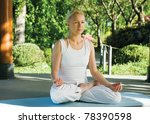 Woman exercising yoga in park - stock photo