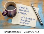 Small photo of Don't be afraid of change. It's going to happen anyway. Handwriting on a napkin with a cup of espresso coffee