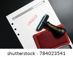 Small photo of Red stamp with text cancelled on business to do list table on black background. Reminder to cancel business appointment. Business cancelled rejected abort declined cancellation denied concept.
