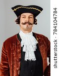 Small photo of mustachioed eccentric man in the vintage clothes of the baron. Hat tricorn, brown jacket. Funny pigtail hair. man dressed as a courtier