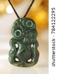 Small photo of Traditional Maori Hei Tiki Jade pendant from New Zealand with eyes inlay from the Shell of the Abalone Sea Ears