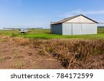 Small photo of Farm airstrip aircraft plane outside hangar in rural countryside.