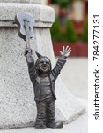Small photo of WROCLAW - POLAND, JUNE 12, 2017 : Wroclaw dwarf, small fairy-tale bronze figurine on the side walk, guitarist. There are over 350 dwarfs spread all over the city, they are a big tourist attraction