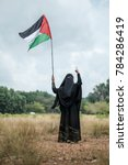 Small photo of A young teenage Muslim girl wearing abaya and hijab holding a Palestine flag