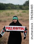 """Small photo of A young Muslim female teenager wearing hijab and headscarf with Arabic sign meaning """"Brigade AlQassam"""" which related to an army group under Hamas, while holding a Palestine sign mafla"""