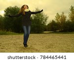 young girl in coat jumps on the ... | Shutterstock . vector #784465441