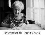 an elderly woman fills a... | Shutterstock . vector #784597141