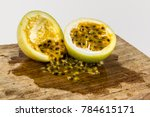 Small photo of Two halve of a pssion fruit one empty and other full of seeds in a piece of wood
