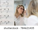 woman trying on glasses in... | Shutterstock . vector #784621435