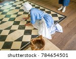 Small photo of Williamsburg, Virginia, USA - 6/21/2009: A woman cleaning a floor in a home in Williamsburg, Virginia. She is dressed period clothing as a scullery maid.