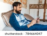 man sitting in bed relaxed at... | Shutterstock . vector #784664047