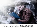 Young Man Reading Book In Old...