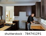 Stock photo carpenter installing cabinets and counter top in a kitchen and partially installed 784741291