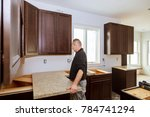 Stock photo contractor installing a new laminate kitchen counter top 784741294