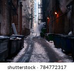 A person stands ate end of an alley where smoke is filling the background of the photo,