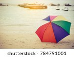 rainbow color umbrella on beach.... | Shutterstock . vector #784791001