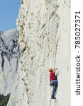 Small photo of Rock climber ascending a challenging cliff. Extreme sport climbing. Freedom, risk, challenge, success.