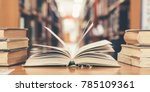 Small photo of Book in library with old open textbook, stack piles of literature text archive on reading desk, and aisle of bookshelves in school study class room background for academic education learning concept