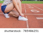 Small photo of Woman runner tying shoelace on running racetrack .
