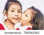 Small photo of Happiness twins girls, cute Asian girl kissing her sister. Concept of Children day, Valentine day, Christmas, family and sisterly love. Profile side view of sisters playing.