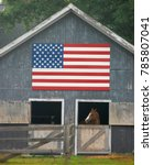Small photo of Horse looks out of stall from patriotic barn.