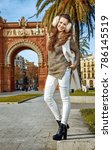 Small photo of in Barcelona for a perfect winter. Full length portrait of smiling modern fashion-monger in earmuffs near Arc de Triomf in Barcelona, Spain