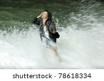 courageous asian woman getting dressed standing in  rough breaker at night, motion blurry