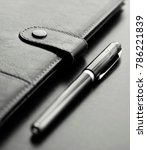 Small photo of Close-up of a black personal agenda and with a pen with selective focus
