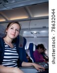 Portrait of a pretty young female passenger on board of an aircraft while on the flight - stock photo