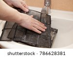 Small photo of Dusty air conditioner filter in male hands. Put in sink flush the mesh with. Clean to get rid of any accumulated dirt