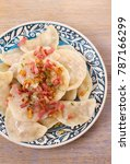 Small photo of Dumplings with filling: cabbage and carrot, served with bacon and onion. Varenyky, vareniki, pierogi, pyrohy. Vertical, overhead