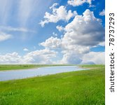 green grass with river under cloudy sky - stock photo