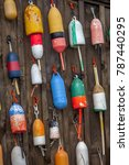 Small photo of Owl's Head, Maine, USA - 8/23/2015: Lobster buoys hang on the exterior wall of a fishing shack. Each one is painted in a uniquely colourful design to identify its licensed lobster fisherman owner.