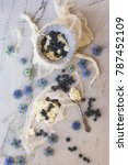 Small photo of Homemade ricotta cheese making with cheese cloth & blueberries on white marble background with decorative blue Nigella damascena flowers also known as love-in-a-mist, ragged lady or devil in the bush.