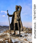 Small photo of KURKUT MOUNTAIN, IRKUTSK REGION, RUSSIA - MARCH 4, 2017: Bronze statue of Transbaikalian tramp. A barefooted traveler standing on a tubercle looks into the distance holding a staff in his right hand
