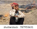Small photo of Gia Lai , Vietnam - March 12, 2017: Old man sit on field with fire made with dry rice straw in Gia Lai, central highland of Vietnam. Drought keep happening in the area for recently years.