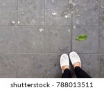 Foots in white shoes and black pants on the dirty floor, bird poop, leaf