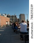 Small photo of New York City - 26 June 2017: People sitting outside on picnic tables at the rooftop bar of the lux Arlo Soho Hotel in Manhattan New York. Shallow depth of field.